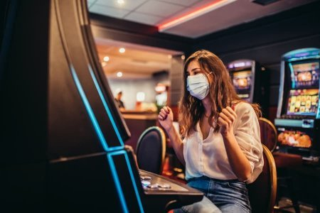 Woman in Mask Playing Slot Machine in Casino